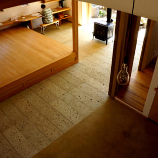 ロフトから見下ろす食堂と居間。土間の床は、深岩石と真砂土三和土仕上げ。板間の床は杉縁甲板の4㎝と厚くしっかりしたもので、踏み心地がよく調湿性・保温性も高い