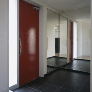 御影石と赤いドアがモダンな玄関スペース。壁全面に鏡が貼られ、空間に拡がりをもたらすともに、姿見として実用性も兼ねている