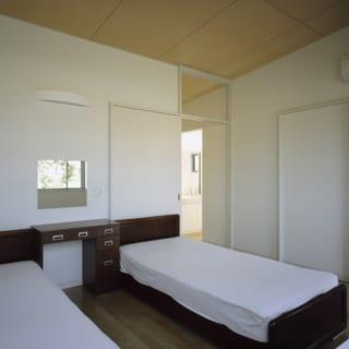 シンプルにしつらえられた寝室。収納たっぷりのウォーキング・クローゼットが隣接している