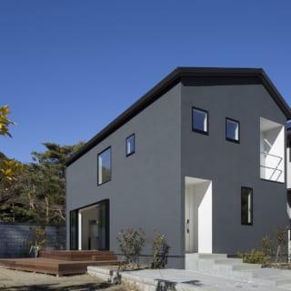 E邸の外観。濃いブルーグレーを基調に玄関や2階のバルコニーなどが白く塗られており、建物にメリハリだけでなく、温かみを感じさせる