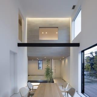 アイランドキッチンからの眺め(日中)。開放的な空間が広がっており、ウッドデッキも視界に入る。また、天井には間接照明が仕込まれている