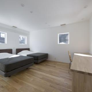 寝室の窓からは朝日が差し込む。写真右の幅が2.6mもあるデスクは移動させることも可能。既製品ではなく、建物のイメージに合わせてつくられた逸品だ