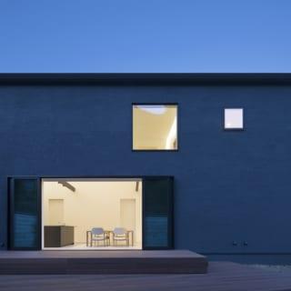 ウッドデッキの方向から見たE邸。濃いブルーグレーの外壁に暖色系で彩られた室内空間が浮かび上がり、住まう人のぬくもりを感じさせる