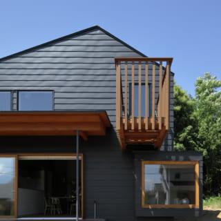 正面からM邸を望む。道行く人たちからMさんご一家の暮らしが見て取れる。1階の縁側と2階デッキは手前に大きくせり出しているだのが、それを感じさせないデザインだ