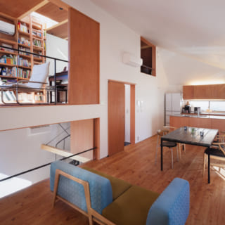 LDKにおいてキッチン方向を見たところ。キッチンはラワン材での造作。左手上にはライブラリーが見える