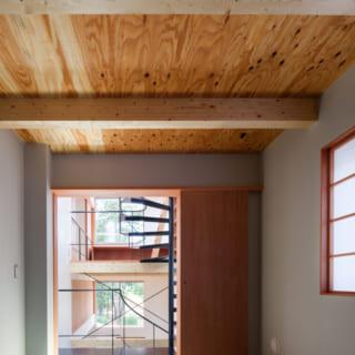 ホール二階の奥にある和室からのホールの見返し。縁なし畳に青い和紙の壁紙。天井は、梁と合板があらわしとなっている