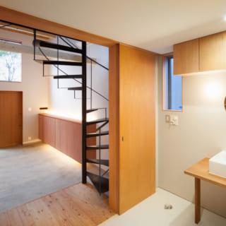 1階洗面室。建具を開け放ちホールを見た所。「トイレ、水周りであっても明るく眺めが良いということを優先したい」というお建主様のご意向でこのようなオープンな洗面室が実現した