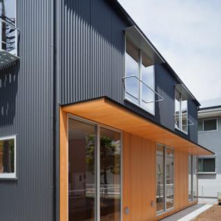 軒下。1階建物東側は、個室が三室並び、個室の外側には外壁と軒裏にピーラー材が貼られた軒下空間が。2階の二つの窓には布団干し用のバーが設けられている