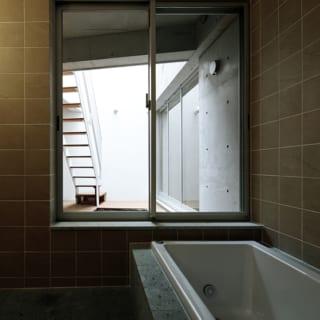 K邸のバスルーム。上原さんがお薦めする十和田石が随所に用いられつつも、部分的にタイルが使われている