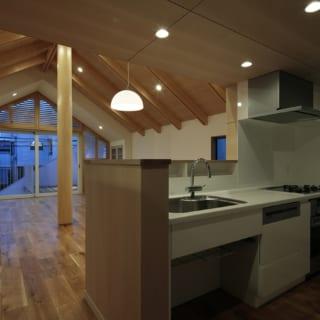 K邸のキッチンから外を見た眺め。1本の梁の中心を削り、2本に見えるようなつくりになっているだけでなく、軽快感も演出する。左側にはサービスルームとバルコニーが備えつけられている