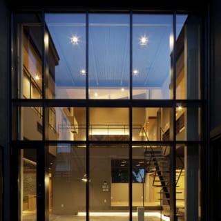 吹き抜けのガラス張りのリビングは、高級感と開放感を両立している。まるで美術館のギャラリーのようだ