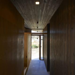 一度景色をシャットアウトするようなイメージでつくったという玄関。塗装した板ではなく焼き杉が用いられている