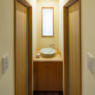 M邸の手洗い場。左右にある扉の奥はトイレだ。桜の花が描かれた焼き物の洗面ボウルや木材など、