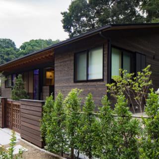 細い路地の一角に佇む、M邸の外観。杉板を用いた外壁が自然に調和している。格子状の引き戸はMさんのこだわりだ