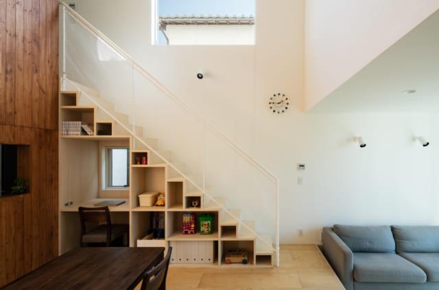 階段下のスペースを有効活用した収納棚。デスクが置かれている場所には小窓があり、昼間は電気を使わなくてもよいほど明るさを保つ