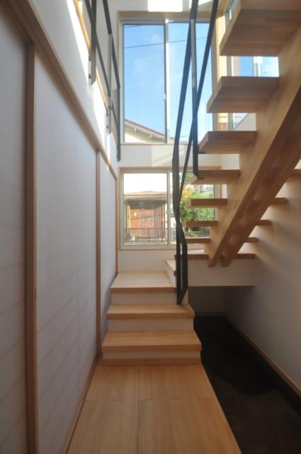 階段踊場下にエアコンが設置されており1階床下全面に吹き込んだ暖気が各部屋の床通気口から吹出す簡易全館空調になっている。左側の障子の向こうはご両親が住む1階のスペースだ
