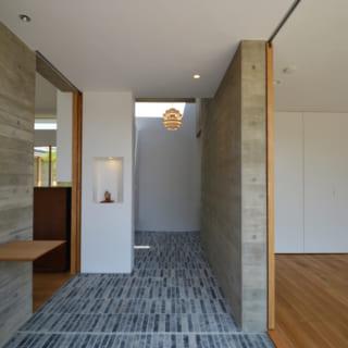 玄関から奥の納戸・書斎へと続く廊下。入って右手が客間、左手がリビングに。木目模様のコンクリートの風合いも良い