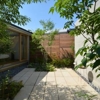 リビング北側の庭。大きめの花崗岩が敷き込まれていて、テラスのようにも利用できる。庭を通して左手に見えるのが寝室