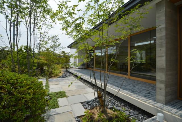 玄関前から南側の庭とテラスを望む。タイルを敷き詰めたテラスの上には庇が張り出し、夏場や雨天でも快適な空間を保つ