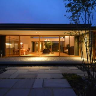 南側の庭から見た夜のリビング。テラスから屋根まで水平垂直でデザインされ、余計なものがないシンプルな空間が美しい
