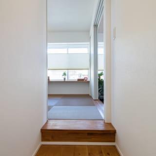 階段から真っ直ぐ進むと和室。右手にLDKがある。和室は天井高を抑えるために1段高くなっている