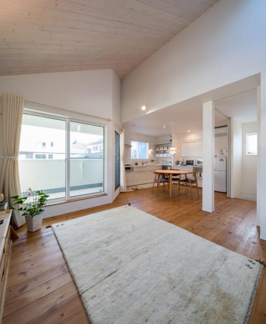 建物の内装はホワイトが基調。リビングの勾配天井に張り込んだ板は、木目を上に向けることで高さを強調している