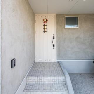 居住部へのアプローチと玄関。壁はモルタルの上にトップコートで仕上げ。塗りムラっぽく陰影が出た雰囲気がいい