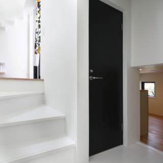 スキップフロアの奥には猫部屋が備えられており、写真の黒い扉(トイレ)を背に半階上ったところに主寝室がある