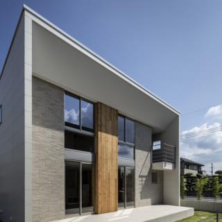 外観 南/屋根と白い袖壁にも、高度な設計スキルが活きている。屋根は雨水を流せるよう、北から南に向けて高くなった片流れ。そのため南の屋根の切り口は、2階の天井から直線でつなげると1m近い厚みが出てしまう。「それでは外観が不格好になってしまう」と、松岡さんは屋根の先端が徐々に薄くなるよう緻密な設計を行った。袖壁と屋根の切り口の厚みを揃えたおかげで、すっきりと美しい門型に仕上がっている