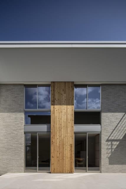 外観 南/庭に面した南の外観。左右のタイルと中央のスギ板を上下一直線の大胆なデザインにし、シンメトリーな安心感と、どっしりとした縦のつながりを表現。上下階の窓の間の外壁は、窓サッシに似たガルバリウム鋼板をセレクト。窓部分も上下の分断を感じさせないのびやかなデザインにこだわった