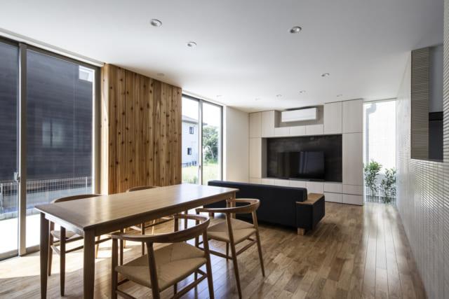 1階 ダイニング・リビング/陽光をたっぷり採り込む2つの掃き出し窓の間の内壁はほかの壁と仕上げを変え、白いクロスではなくスギ板を使用した。表から見ても室内から見ても、同じ位置に同じ幅で同じスギ板がある仕掛け。こうすると「壁の間に窓がある」印象がなくなり、庭とリビングの一体感が高まる。また、写真奥のテレビ台横にはキッチンの壁に沿ったスリット窓も。リビングに入るときに視線が抜け、空間を広く感じる効果がある