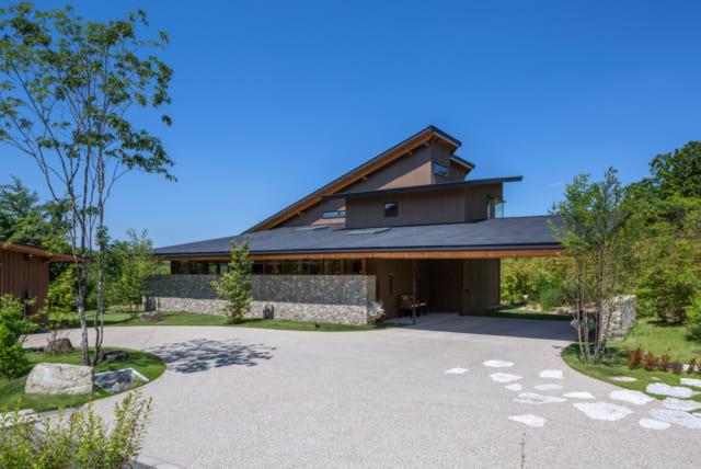 S邸のファサード。石積み屏と低く抑えられた大屋根が印象的だ。写真の左に見える小屋は庭仕事の道具などを収容