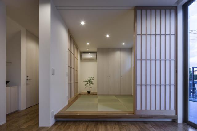 1階 和室/盆栽の横の障子を開けると玄関に直結する設計。面積的に玄関を大きくとるのが難しかったため、ディスプレースペース、客間など、さまざまな使い方ができる和室をつくって空間を有効活用。この和室で「玄関まわりにひな人形などを飾るスペースが欲しい」との要望に応えた。家族構成に変化があれば主寝室としても使用可能