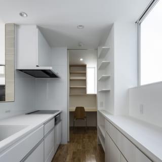 1階 キッチン/収納豊富で使いやすいキッチン。奥にはカウンターデスク付きの家事スペースがあり、冷蔵庫も置ける。コンロや調理台との距離が近く動線抜群だが、キッチンはすっきり。ストック食材などの保管もでき、重宝する空間