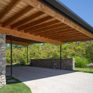 玄関に直結したカーポートには車が2台停められる。大屋根と石塀により風景を切り取ってみせるフレーム効果も