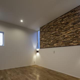 2階 主寝室/2つの窓の間に寄木の木製パネルをしつらえ、「壁に囲まれた」印象を軽減。また、木製パネルは微妙に壁から浮いて見えるように設計されているため、「壁っぽさ」がさらになくなり、閉塞感とは無縁なくつろげる寝室に。窓の下の間接照明は、2つのベッドを入れたとき、それぞれの手もと灯にもなる