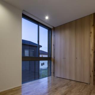 2階 子ども部屋/子ども部屋は2室あり、収納の向こうはもう1室の子ども部屋。収納の引き戸は部分的に外壁と同じスギ板を用いて屋外とのつながりを意識。将来を鑑み、お子様が独立した際は、収納とドアを外すと1つの大きな部屋として使えるように設計した