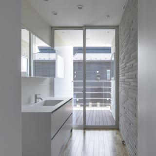 2階 洗面室からバルコニーを見る/バルコニーに出る窓は、天井際と両脇の壁際まで大きく開口。屋外と一体感のある半戸外空間となった。右の壁のタイル、左の壁の白いサイディングは外壁と連続しており、「外とつながっている」印象が強調され、開放感がますますアップ