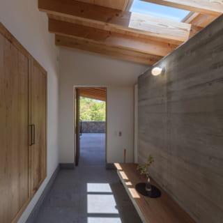玄関内部から駐車場の眺め。トップライトを設けた玄関ホールには白河石を敷いている。右側の壁の裏はクローク