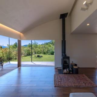 暖房はこの薪ストーブと床暖房でまかなっている。天井のアールと間接照明は、宮崎さんのこだわりだという