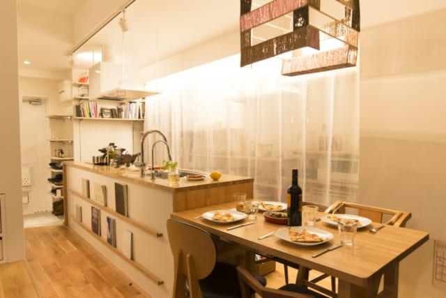 ゆっくりディナーを楽しみたいときには、キッチンのカーテンを引く。間接照明の光に包まれて、昼間とは違った雰囲気が醸し出される