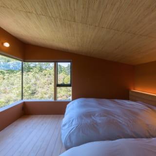 主寝室。オーディオルームとこの部屋の天井には葦を使用。葦の表情を活かすため間接照明とした
