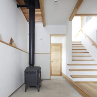 玄関を入ったところにある土間には薪ストーブ。ここから暖気が上に上がり、部屋全体を温めてくれる