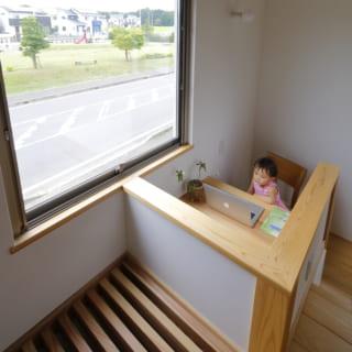踊り場に設けられたスタディスペースは、子どもの勉強机としても利用可能。その手前のルーバーの下には薪ストーブがあり、ここから暖気が上に上がってくる仕組み