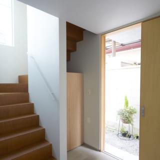 階段をらせん状にして、その下のスペースを下駄箱として利用。傾斜を緩めても多少の勾配がついてしまう階段には手すりを備え付けてある