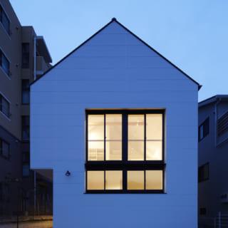 外観 夕景/三角屋根に白い壁。子どもが描く「おうちの家」そのままのような、愛らしくてホッとする外観。上下階で開口の幅をそろえてあり、まるで1つの大きな窓のよう。2階のLDKを広くしたため、1階の左が少し凹んでいるが、屋根の重みを家の中心に流す設計で外柱が不要になり、シンプルでかわいらしいシルエットが実現した。ここには玄関があるので雨の日の庇(ひさし)がわりにもなるそう