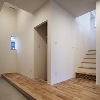1階 玄関まわり/横長の広い玄関土間。ここには、現在、C様の趣味のマリンスポーツの道具がずらりと並べられている(写真は竣工時のもの)。C邸は玄関と階段を中心に、家の半分は3層、もう半分は2層のスキップフロア構造。階段の北側(写真左側)は3層構造で、1層目は階段手前に入口がある半地下の収納スペース。階段を上がった左手は2層目となる洗面室・バスルーム。その上には3層目となる個室とウォークインクローゼットがある