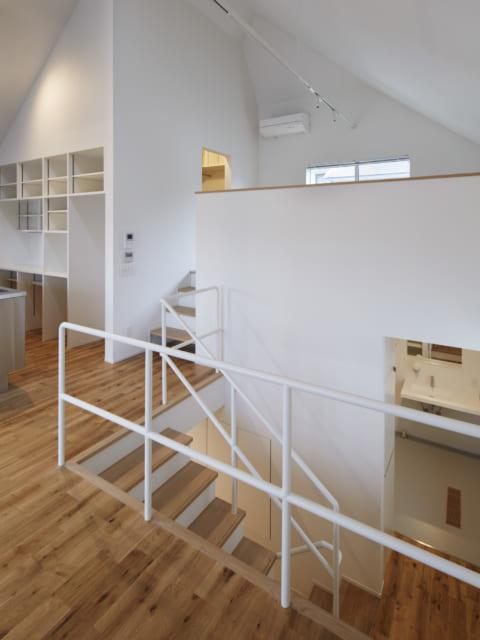 2階 階段/階段に接した低い壁の向こうは、LDKから半階上がった個室。その左手にはウォークインクローゼット