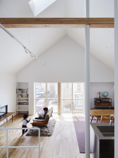2階 LDK/三角屋根の形を活かした開放的なLDKは、南向きで採光抜群。最大の天井高は約5mもある。上部には、温かみのある木製の梁や天窓が。青空を望む天窓からは自然光が差し込み、冬でも明るい。これだけの大空間は冬季に寒くなりがちだが、関さんの『魔法びん化』設計と高気密のおかげで、年間を通して快適に過ごせる