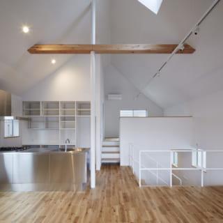 2階 リビング窓側からキッチン、個室を見る/LDKと半階上の個室が、高い天井の下で1つにつながるおおらかな空間。床の高さが異なるため、「違う空間」としての独立性も保たれ、ちょうど良い距離感